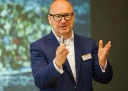 Keynote Speaker Axel Liebetrau mit Präsentation im Hintergrund
